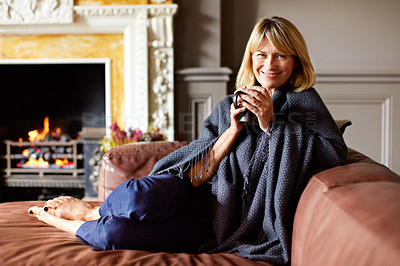 Buy stock photo Shot of a mature woman sitting on her sofa drinking tea while wrapped in a blanket
