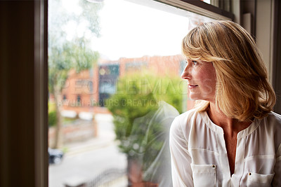Buy stock photo Cropped shot of a mature woman looking out of her living room window