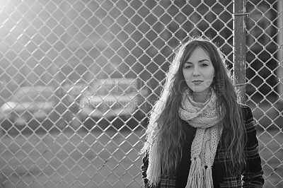 Buy stock photo Black and white shot of a young woman posing outdoors against a mesh wire fence