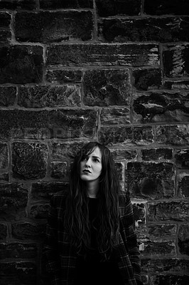 Buy stock photo Black and white shot of a young woman posing outside against a brick wall