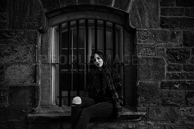 Buy stock photo Black and white shot of a young woman sitting outside on a window sill