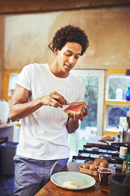 Buy stock photo Shot of a young man making breakfast at home