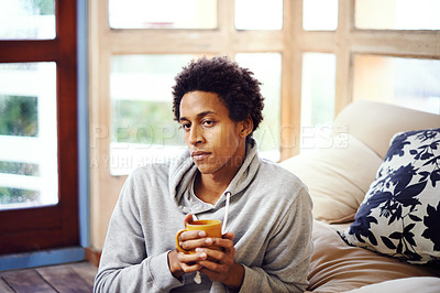 Buy stock photo Shot of a young man drinking a warm beverage at home