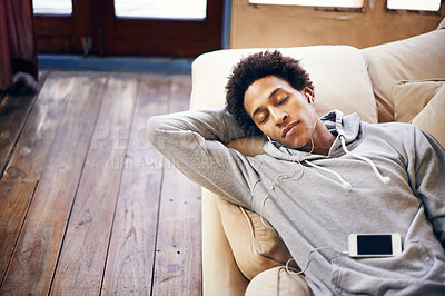 Buy stock photo Shot of a young man relaxing on his sofa listening to music