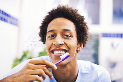 Buy stock photo Shot of a young man brushing his teeth in the bathroom