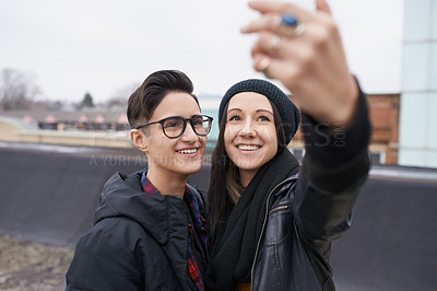 Buy stock photo Shot of a young couple taking a selfie outdoors