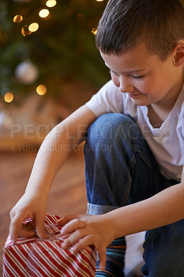 Buy stock photo Shot of a little boy wrapping Christmas presents at home