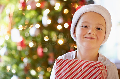 Buy stock photo Portrait of a happy little boy holding a Christmas present at home