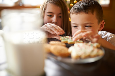 Buy stock photo Shot of a brother and sister peering at freshly baked Christmas cookies on a table