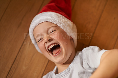 Buy stock photo Shot of a little boy wearing a santa hat and laughing delightfully while playing on the floor