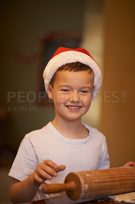Buy stock photo Shot of a happy little boy baking at home during Christmas