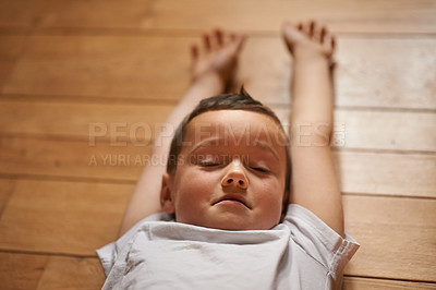 Buy stock photo Shot of a little boy relaxing on the floor at home