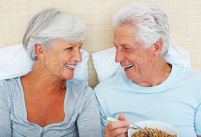 Buy stock photo Closeup of senior couple smiling and looking at each other with man having breakfast in bed