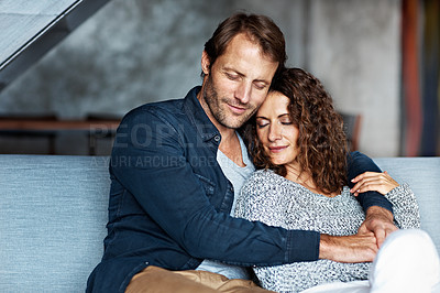 Buy stock photo Shot of an affectionate mature couple in their living room