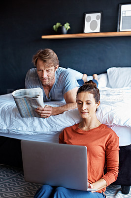Buy stock photo Shot of a mature couple using a laptop and reading the newspaper while relaxing in their bedroom