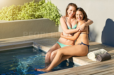 Buy stock photo Shot of two friends in bikinis hugging each other and laughing while sitting by a swimming pool