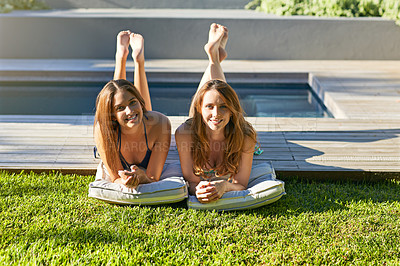 Buy stock photo Shot of two friends suntanning together next to a swimming pool