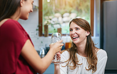 Buy stock photo Shot of two friends hanging out in a kitchen drinking wine together