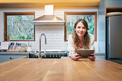 Buy stock photo Portrait of a young woman leaning on her kitchen counter using a digital tablet