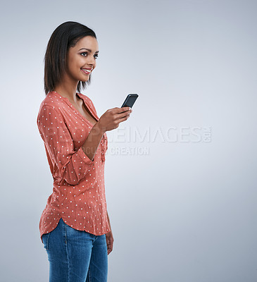 Buy stock photo Studio shot of a young woman using a cellphone against a grey background