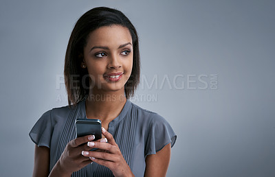 Buy stock photo Studio shot of a young woman using a phone against a gray background