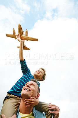 Buy stock photo Shot of a boy playing with a toy airplane while getting a piggyback from his father outside
