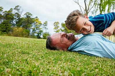 Buy stock photo Shot of a laughing father and son lying on grass