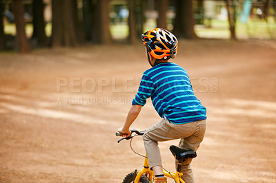 Buy stock photo Rearview shot of a little boy riding a bicycle through a park