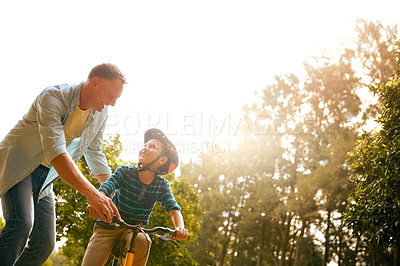 Buy stock photo Shot of a father teaching his son how to ride a bicycle