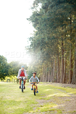 Buy stock photo Shot of a father and son riding bicycles in a park