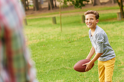 Buy stock photo Shot of a father and son throwing a football in a park