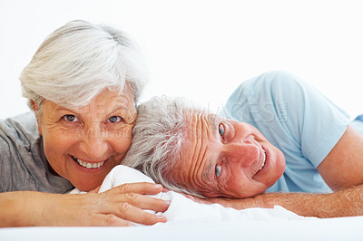 Buy stock photo Closeup portrait of happy senior couple lying in bed and smiling