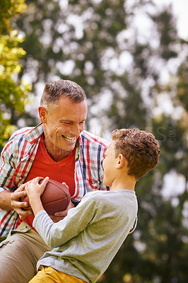 Buy stock photo Shot of a father and son playing football in a park