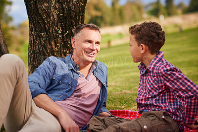 Buy stock photo Shot of a father and son talking together while lying in a park