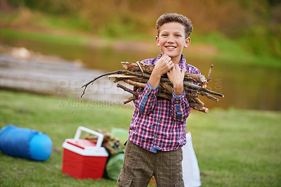 Buy stock photo Portrait of a young boy carrying a bundle of sticks for a fire while camping