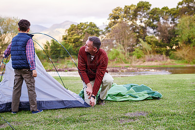 Buy stock photo Shot of a father and son setting up a tent together while camping