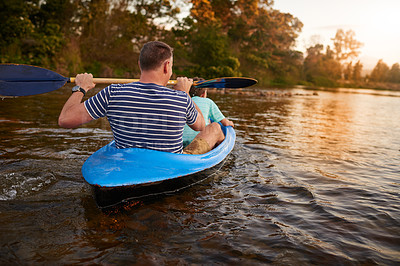 Buy stock photo Shot of a father and son rowing a boat together on a lake
