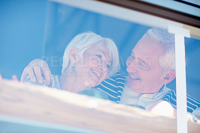 Buy stock photo Shot of a senior couple talking together at a cafe window