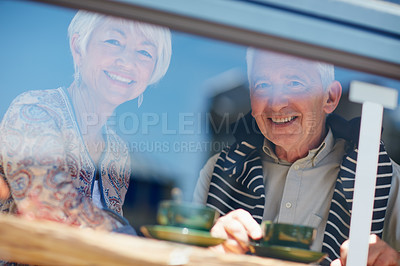 Buy stock photo Portrait of a senior couple talking together at a cafe window