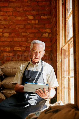 Buy stock photo Cropped shot of a senior man using a tablet while working in a roastery