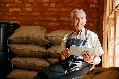Buy stock photo Cropped portrait of a senior man using a tablet while working in a roastery