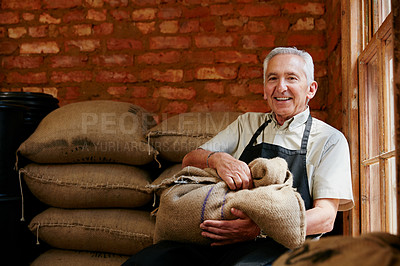 Buy stock photo Cropped portrait of a senior man holding a sack of coffee beans while sitting in a roastery