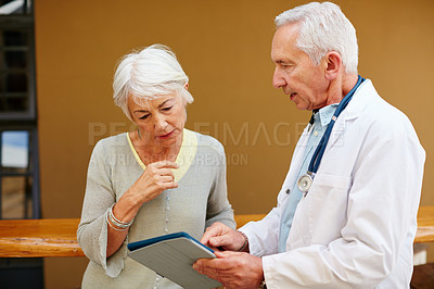 Buy stock photo Shot of a senior woman discussing test results with her doctor on a digital tablet