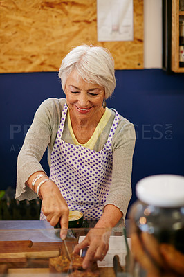 Buy stock photo Shot of a senior woman cutting a slice of cake in a bakery