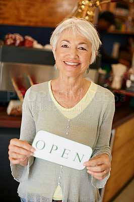 Buy stock photo Portrait of a senior woman holding up a sign on opening day of her small business