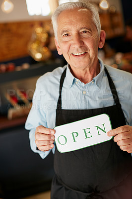 Buy stock photo Portrait of a senior man holding up a sign on opening day of his small business