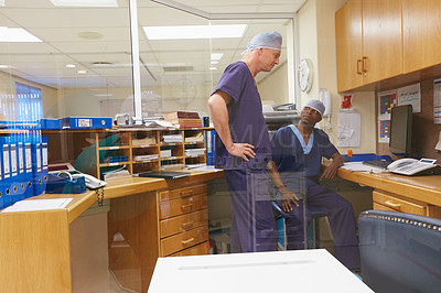Buy stock photo Shot of two surgeons having a discussion in a hospital