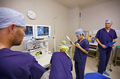 Buy stock photo Shot of a team of surgeons preparing for a surgery