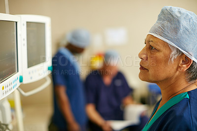 Buy stock photo Shot of a surgeon looking at a monitor in an operating room