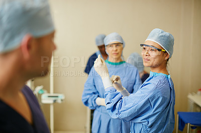 Buy stock photo Shot of surgeons putting on surgical gloves in preparation for a surgery